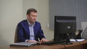 Jonge zakenman die in bureau werken, zittend bij bureau, die het computerscherm bekijken stock videobeelden