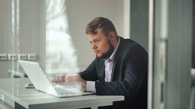 Jonge zakenman die in bureau werken, zittend bij bureau, die laptop het computerscherm bekijken stock videobeelden
