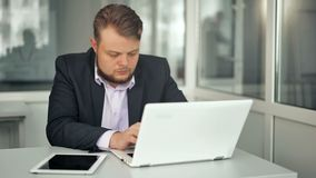 Jonge zakenman die in bureau werken, zittend bij bureau, die laptop het computerscherm bekijken stock video