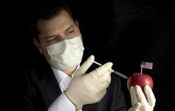 Jonge zakenman die chemische producten inspuiten in een appel met Verenigd stock afbeeldingen