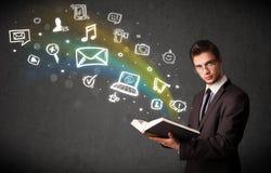 Jonge zakenman die een boek met pictogrammen volgende ou van verschillende media lezen Stock Foto's