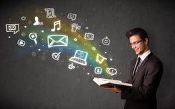 Jonge zakenman die een boek met pictogrammen volgende ou van verschillende media lezen Stock Afbeelding