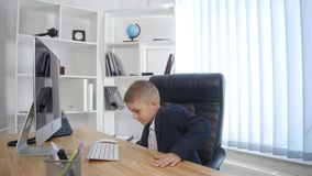 Jonge zakenman die een computer in bureau met behulp van stock footage