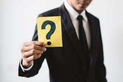 Jonge zakenman die een kaart met VRAAGTEKEN houden royalty-vrije stock afbeelding