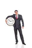 Jonge zakenman die een klok houden Stock Foto