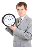 Jonge zakenman die een klok houdt Stock Afbeeldingen