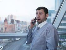 Jonge zakenman die emotioneel op een mobiele telefoon met verbazing op zijn gezicht tegen de achtergrond van een panoramisch vens royalty-vrije stock afbeelding