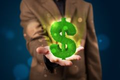 Jonge zakenman die groen gloeiend dollarteken voorstellen Stock Foto