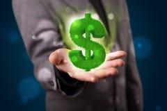Jonge zakenman die groen gloeiend dollarteken voorstellen Stock Afbeelding
