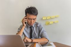 Jonge zakenman die horloge bekijken en op telefoon spreken stock afbeeldingen