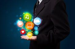 Jonge zakenman die kleurrijke technologiepictogrammen en symbo voorstelt Stock Afbeelding