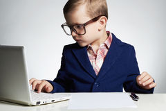 Jonge zakenman die laptop met behulp van Ernstig kind in glazen stock fotografie