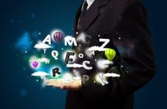 Jonge zakenman die magische wolken met brieven en bal voorstellen Stock Fotografie
