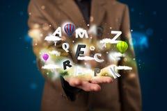 Jonge zakenman die magische wolken met brieven en bal voorstelt Stock Foto's