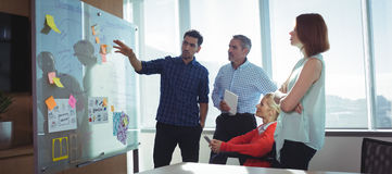 Jonge zakenman die met collega's op kantoor bespreken stock afbeeldingen