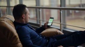 Jonge zakenman die met de tablet werken: het spreken op een celtelefoon stock videobeelden