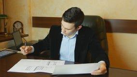 Jonge zakenman die met documenten bij bureau in bureau werken Stock Foto