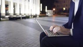 Jonge zakenman die met laptop aan een bank bij nacht zijaanzicht werken stock footage