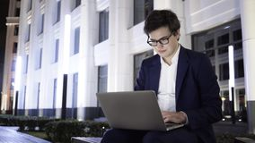 Jonge zakenman die met laptop aan een bank binnen de stad in bij nacht werken stock video