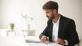 Jonge zakenman die met laptop documenten werken, die bedrijfsboekhoudingstoepassing gebruiken stock videobeelden