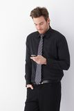 Jonge zakenman die mobiele telefoon met behulp van Stock Fotografie
