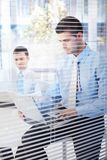Jonge zakenman die in modern bureau werken Stock Afbeeldingen