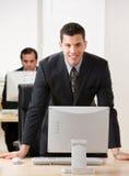 Jonge zakenman die op bureau leunt Royalty-vrije Stock Foto