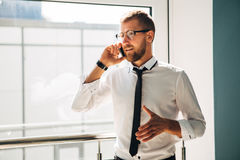 Jonge zakenman die op de telefoon in de hal van het bureau spreken royalty-vrije stock foto