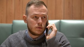 Jonge zakenman die op de telefoon op het kantoor spreken stock video
