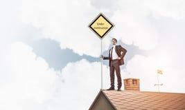 Jonge zakenman die op het dak van de huisbaksteen geel uithangbord houden Stock Fotografie