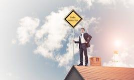 Jonge zakenman die op het dak van de huisbaksteen geel uithangbord houden Stock Afbeelding