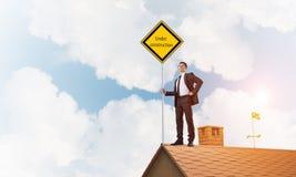 Jonge zakenman die op het dak van de huisbaksteen geel uithangbord houden Gemengde media Stock Afbeelding