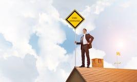 Jonge zakenman die op het dak van de huisbaksteen geel uithangbord houden Gemengde media Royalty-vrije Stock Foto