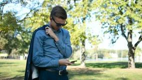 Jonge zakenman die op iemand buiten wachten, gebruikend zijn mobiele telefoonsmartphone op een zonnige dag stock video