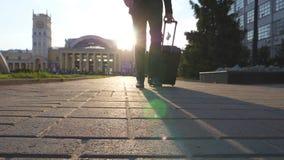 Jonge zakenman die op stedelijk milieu lopen en koffer op wielen trekken Succesvolle zekere manager die gaan met stock videobeelden