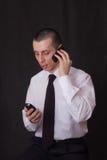 Jonge zakenman die op twee telefoons spreekt Stock Afbeeldingen