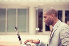 Jonge zakenman die in openlucht gebruikend laptop werken Royalty-vrije Stock Foto's