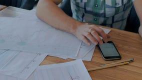 Jonge zakenman die smartphone gebruiken, die bij werkplaats met blauwdruk in koffie zitten stock video