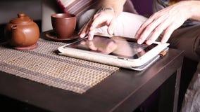 Jonge zakenman die tabletcomputer voor online het winkelen met behulp van Mens die aan PC-tablet en het drinken thee in koffie we stock footage