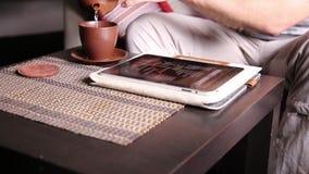 Jonge zakenman die tabletcomputer voor online het winkelen met behulp van Mens die aan PC-tablet en het drinken thee in koffie we stock video