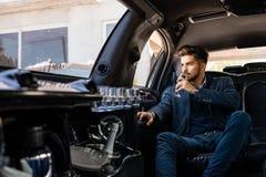 Jonge zakenman die van champagne in limo genieten stock fotografie