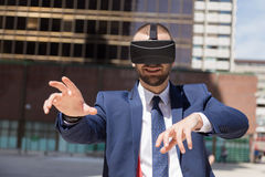 Jonge zakenman die virtuele werkelijkheidsglazen dragen en gest doen Stock Afbeelding
