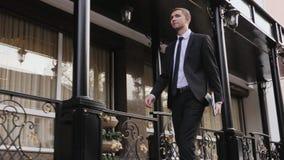 Jonge zakenman die vol vertrouwen onderaan de straat lopen stock footage