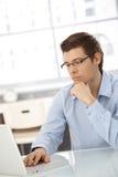 Jonge zakenman die zich op het computerwerk concentreert Stock Fotografie