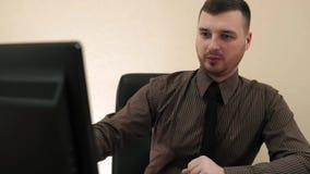 Jonge zakenman die in zijn bureauvideoframe dicht en lage hoek uitwerken stock footage