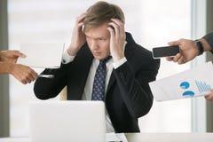 Jonge zakenman die zijn hoofd grijpen stock foto