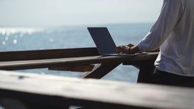 Jonge zakenman die zijn laptop op de waterkant op overzeese achtergrond met behulp van stock footage