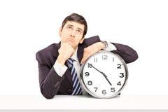 Jonge zakenman diep in gedachten die met een klok op een tabl stellen Stock Foto