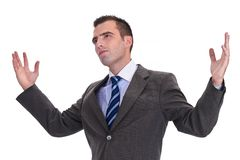 Jonge zakenman in een grijs kostuum met opgeheven handen, die kijken aan stock afbeeldingen