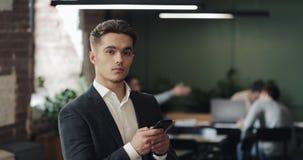 Jonge zakenman in een kostuum die smartphone gebruiken die zich in modern bureau bevinden Mens die de camera onderzoeken Arbeider stock video